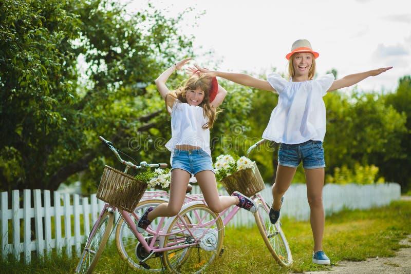 Due belle ragazze felici dei pantaloni a vita bassa che ridono e che posano per la macchina fotografica con le bici fotografia stock libera da diritti