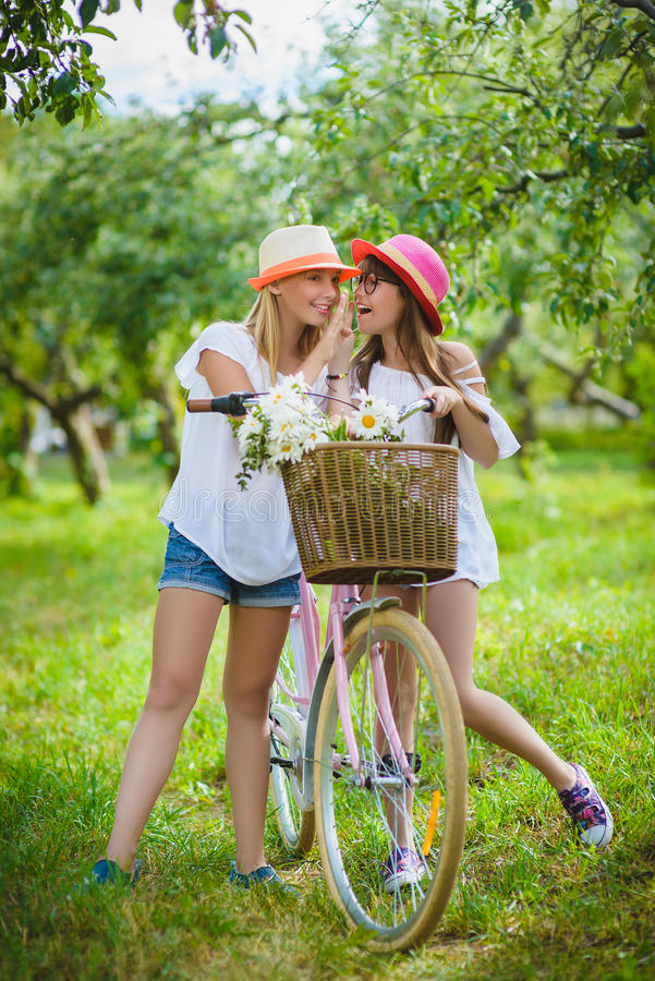 Due belle ragazze felici dei pantaloni a vita bassa che ridono e che posano per la macchina fotografica con le bici immagine stock libera da diritti