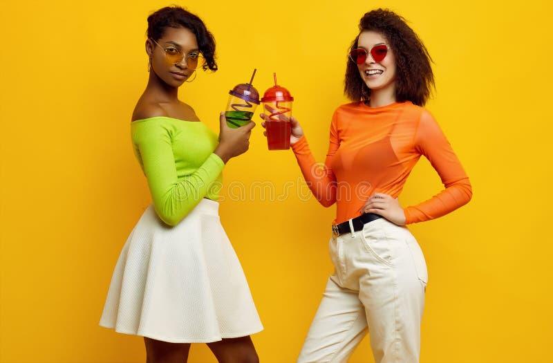 Due belle ragazze hipster in abiti estivi colorati con cocktail immagine stock libera da diritti