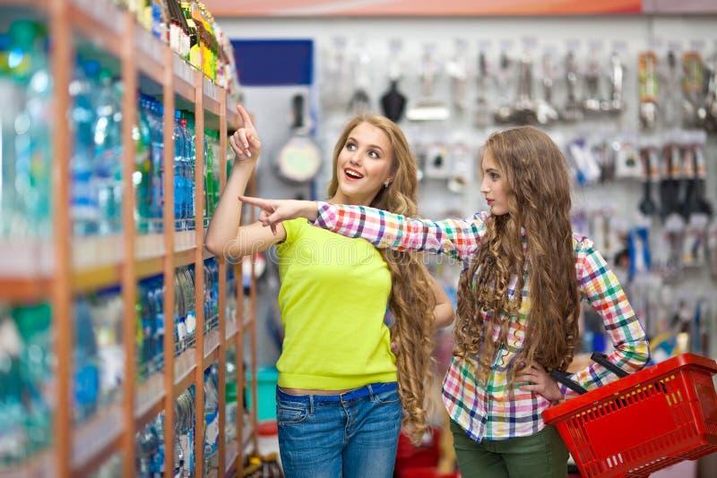 Due belle ragazze si divertono scegliendo gli alimenti nel deposito immagine stock
