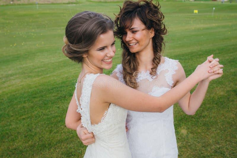 Due belle spose che ballano sul campo verde fotografia stock