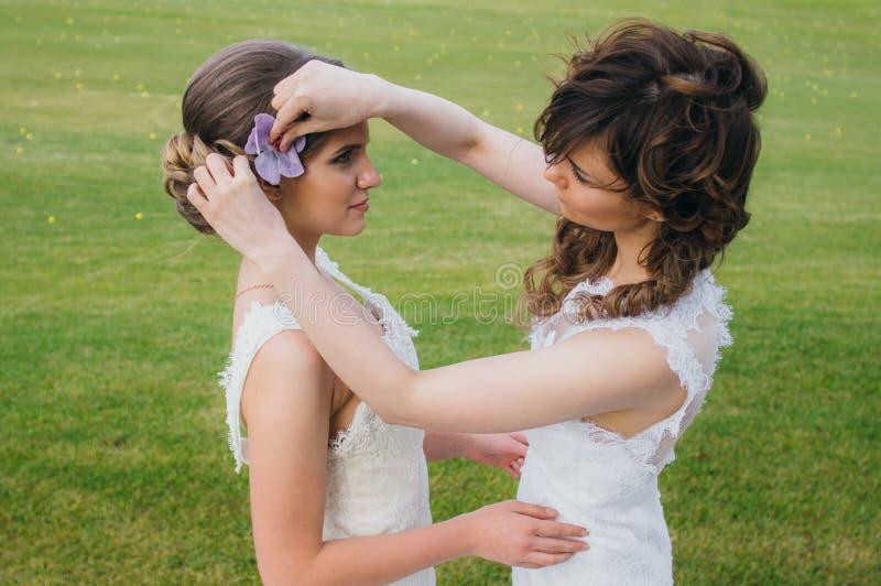 Due belle spose che correggono capelli sul campo verde fotografia stock