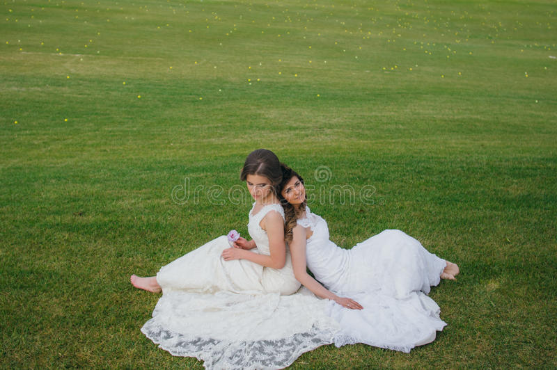Due belle spose che si siedono di nuovo alla parte posteriore sul campo verde fotografie stock