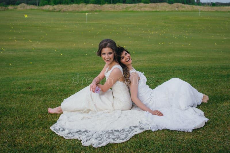 Due belle spose che si siedono di nuovo alla parte posteriore sul campo verde immagini stock libere da diritti