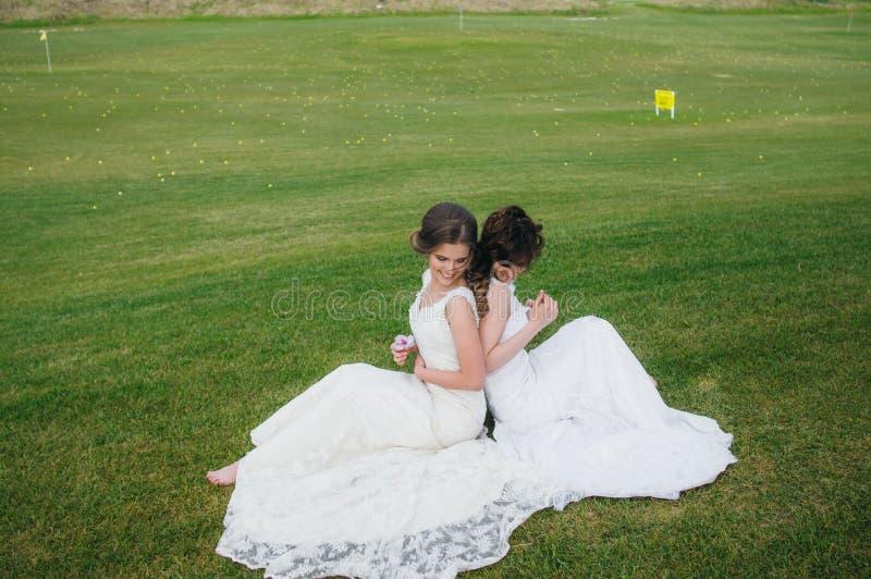 Due belle spose che si siedono di nuovo alla parte posteriore sul campo verde fotografia stock