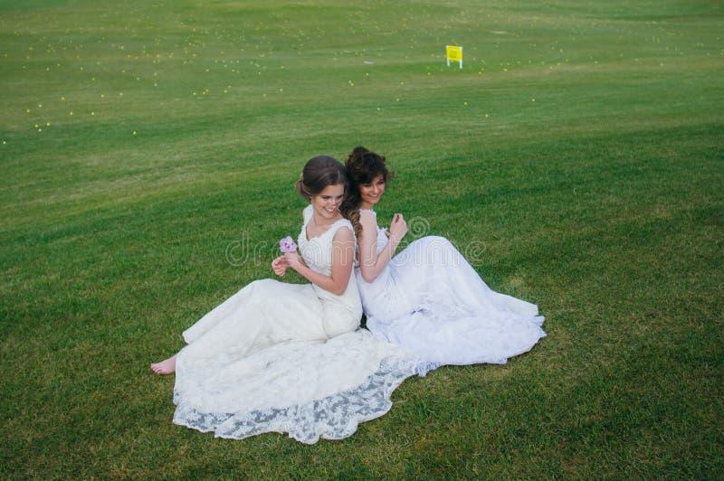 Due belle spose che si siedono di nuovo alla parte posteriore sul campo verde immagine stock