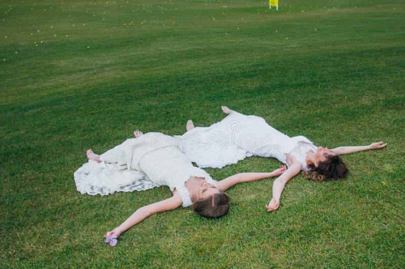 Due belle spose che si trovano sul campo verde fotografia stock libera da diritti