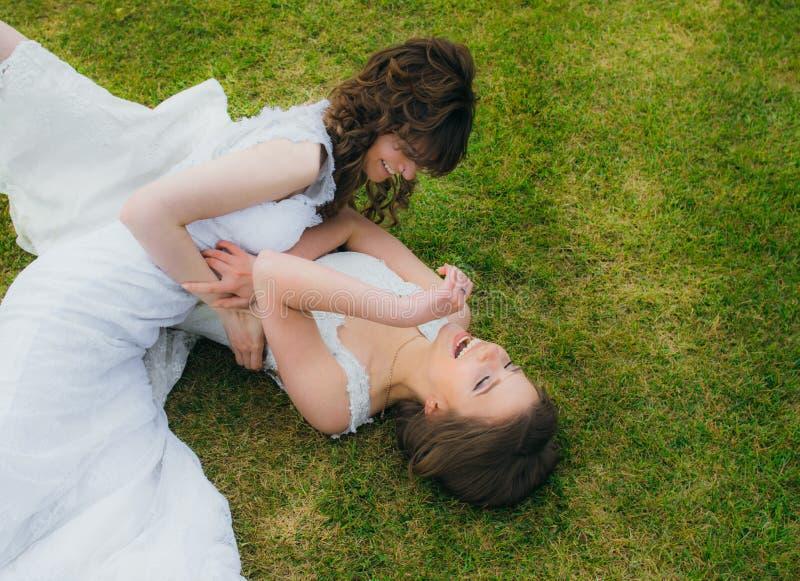 Due belle spose che si trovano sul campo verde fotografie stock libere da diritti