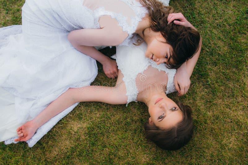 Due belle spose che si trovano sul campo verde immagini stock