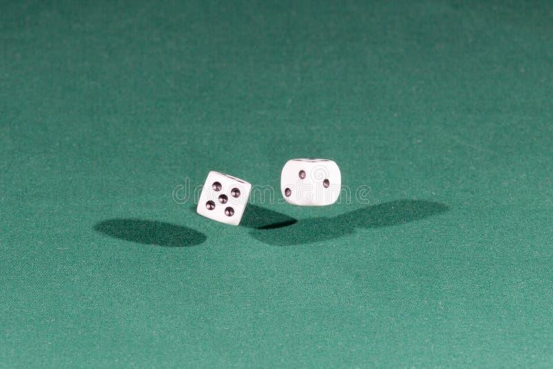 Due bianchi tagliano cadere a cubetti su una tavola verde immagine stock libera da diritti