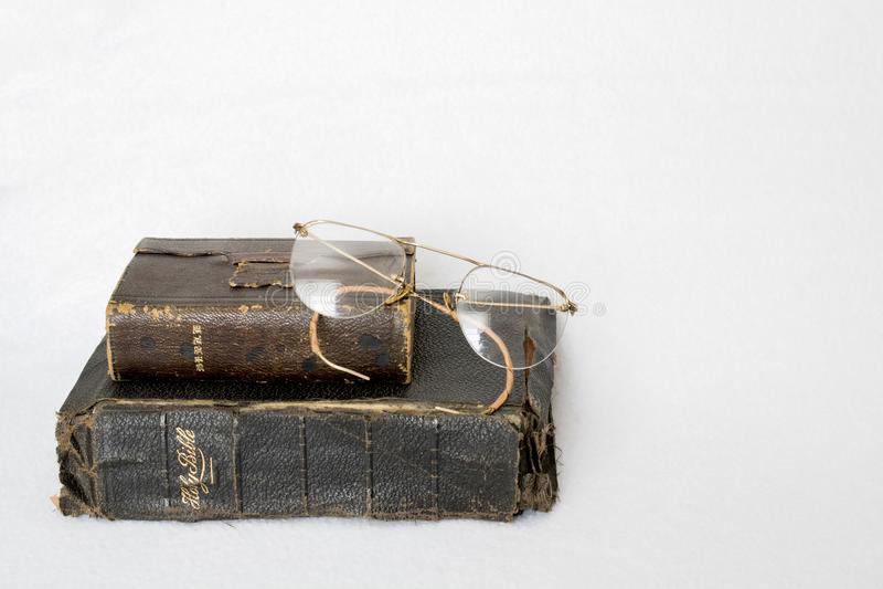 Due bibbie di cuoio antiche con i vetri dell'occhio su fondo bianco fotografia stock libera da diritti