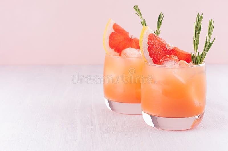 Due bicchieri bagnati freddi di eleganza con il cocktail fresco di estate del pompelmo, ghiaccio, rosmarino su fondo rosa fotografia stock