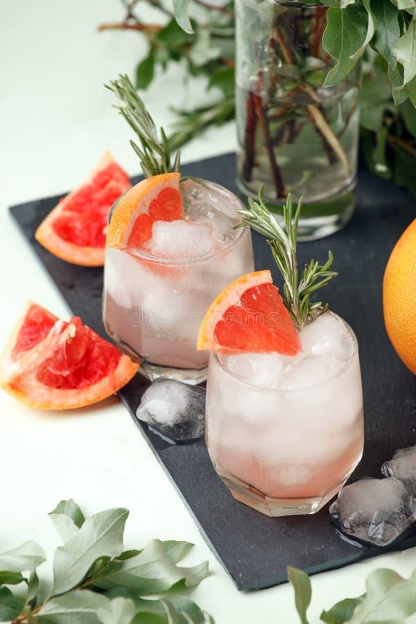 Due bicchieri bagnati freddi di eleganza con il cocktail fresco, il ghiaccio, i rosmarini su fondo di pietra posteriore e la pian immagini stock libere da diritti