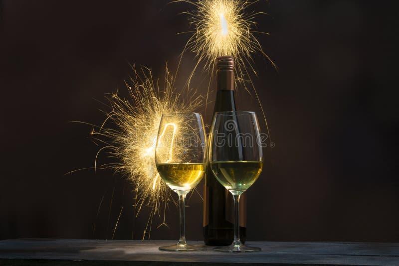Due bicchieri di vino con le bottiglie di vino con il fondo dei fuochi d'artificio immagine stock libera da diritti
