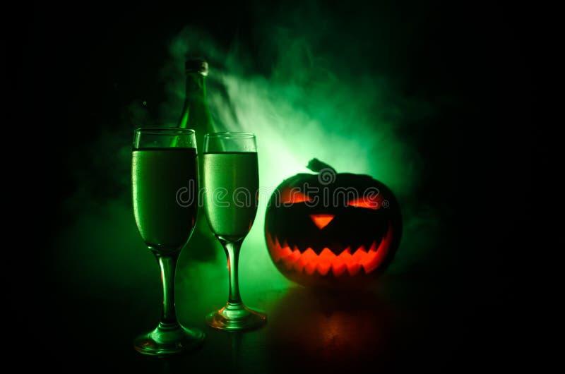 Due bicchieri di vino e bottiglie con Halloween - vecchia presa-o-lanterna su fondo nebbioso tonificato scuro Zucca spaventosa di fotografia stock libera da diritti