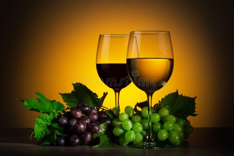 Due bicchieri di vino ed uva su di legno immagini stock libere da diritti