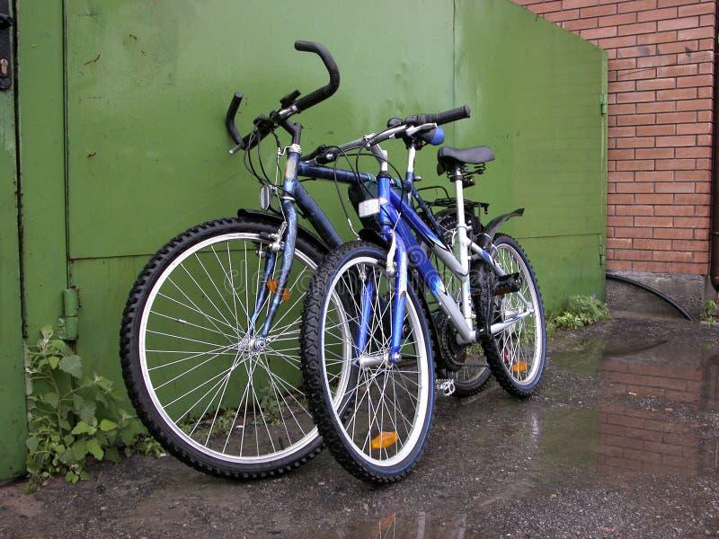 Due biciclette al cancello verde fotografia stock libera da diritti