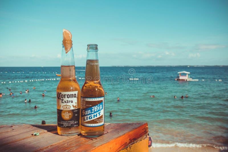 Due birre leggere Corona Extra e San Mig in cima al piano di legno Brown vicino alla spiaggia immagine stock