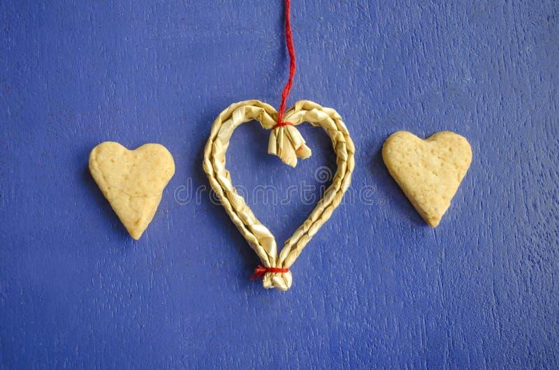 Due biscotti sotto forma dei cuori su un fondo blu e su un cuore d'attaccatura fatti di paglia Fondo di concetto di amore 14 febb fotografia stock libera da diritti