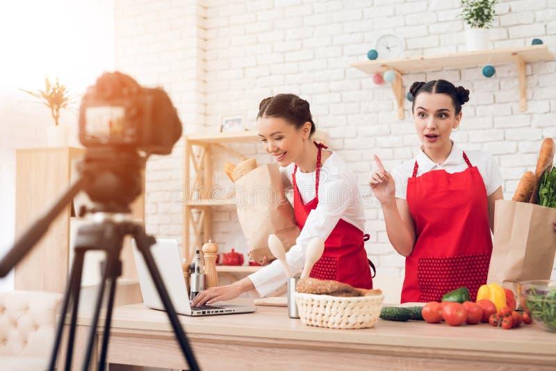 Due blogger culinari ostacolano i packagges con la lettura dell'alimento dal computer portatile alla macchina fotografica immagine stock