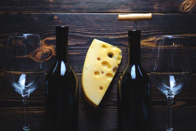Due bottiglie con i vetri di vino e un pezzo di formaggio su un fondo di legno immagine stock