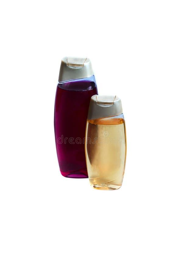 Due bottiglie con la doccia si gelificano nei colori differenti su fondo bianco closeup immagine stock