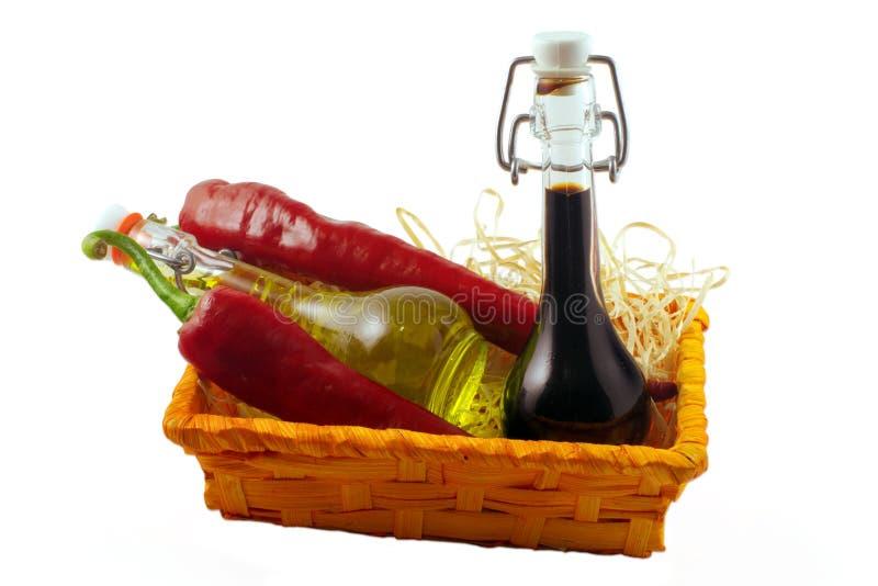 Due bottiglie dell'aceto di vino, dell'olio d'oliva e del pe freddo rovente due immagini stock