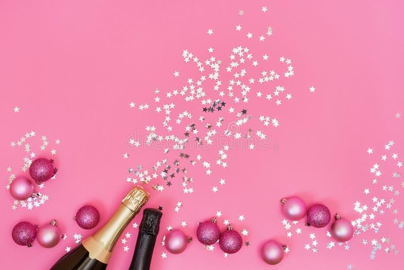 Due bottiglie di Champagne con gli ornamenti di Natale su backgroun rosa fotografia stock
