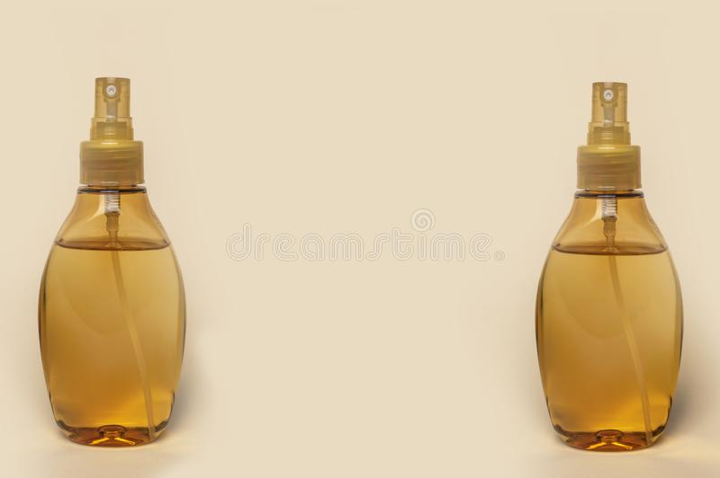 Due bottiglie di plastica con il primo piano giallo dell'olio di massaggio immagini stock libere da diritti