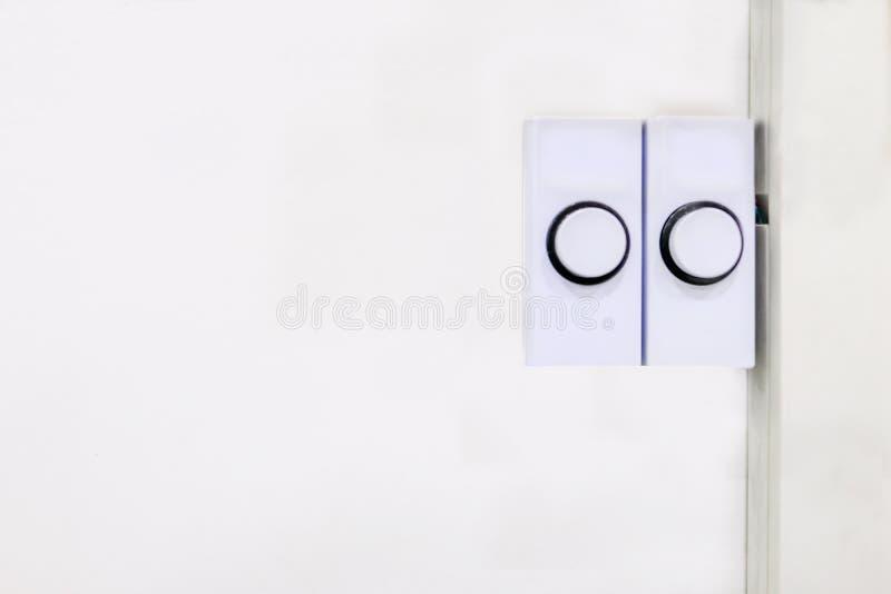 Due bottoni rettangolari di plastica bianchi del campanello per porte pronti affinchè spingere avvisino l'occupante che qualcuno  fotografie stock libere da diritti