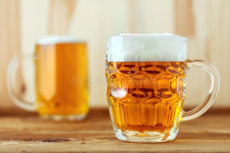 Due brocche piene di birra sul contatore della barra immagini stock