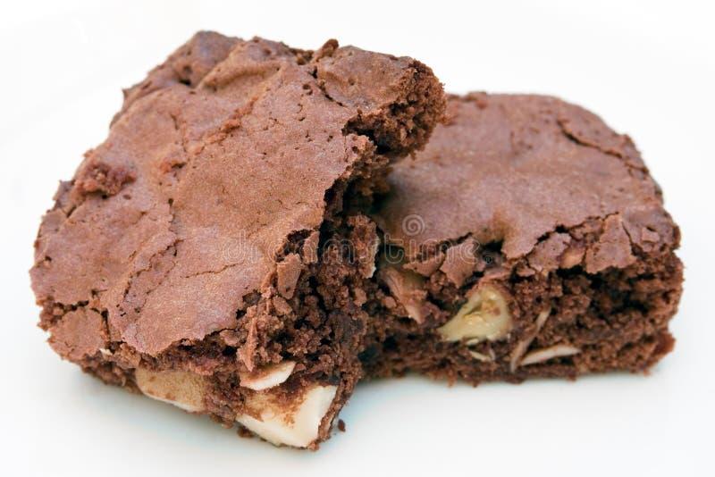 Due brownie del cioccolato impilati insieme su bianco immagini stock