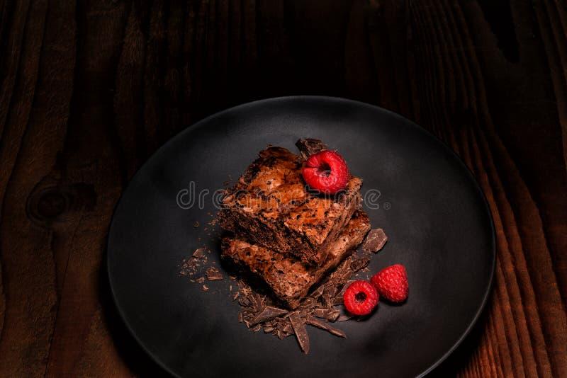 Due brownie e lamponi su una banda nera sulla tavola di legno scura immagine stock