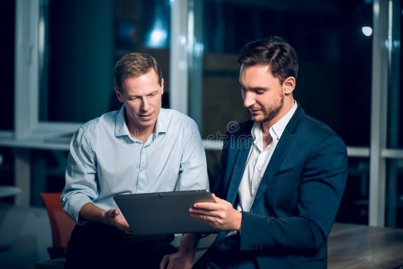 Due busienessmen che lavorano tardi nell'ufficio fotografia stock libera da diritti
