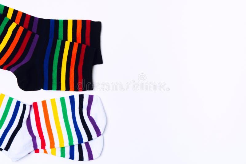 Due calze bianche e nere con pattern a strisce colorate per piedi Indumenti di cotone decorativi con stampe divertenti In alto immagine stock