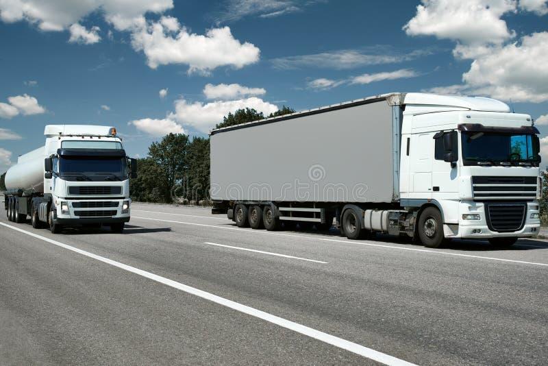 Due camion con il contenitore e la cisterna sulla strada, transportat del carico fotografia stock