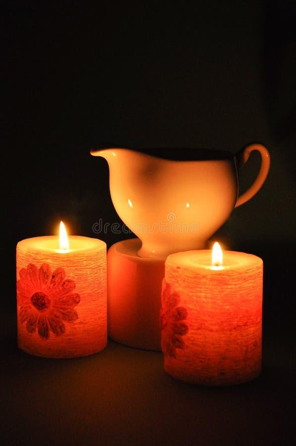 Due candele brucianti e un bollitore della porcellana fotografie stock