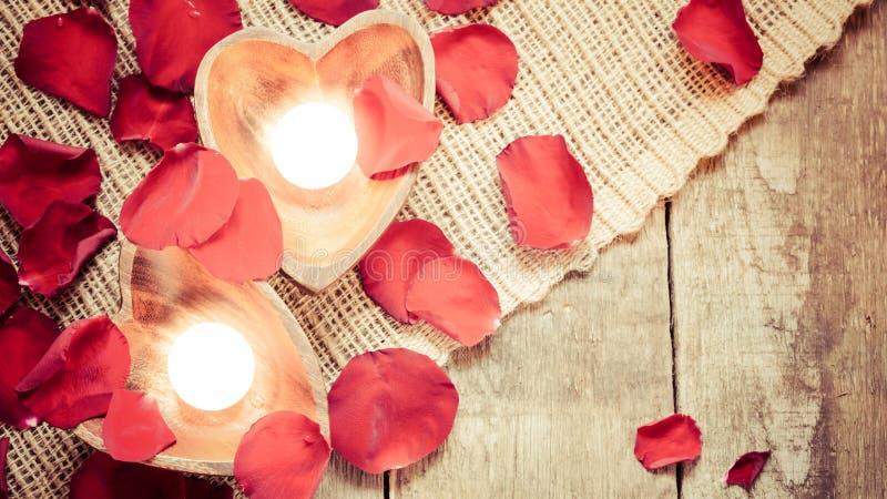 Due candele chiarite in candelieri in forma di cuore con sono aumentato immagine stock libera da diritti