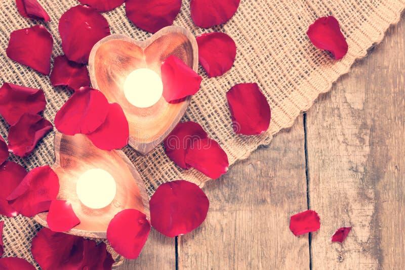 Due candele chiarite in candelieri in forma di cuore con sono aumentato immagini stock