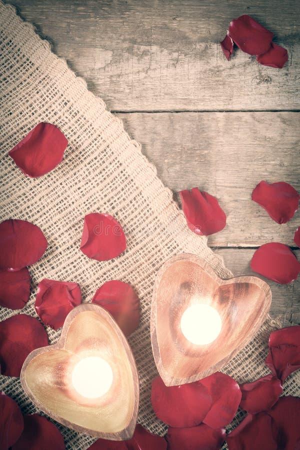 Due candele chiarite in candelieri in forma di cuore con sono aumentato fotografie stock