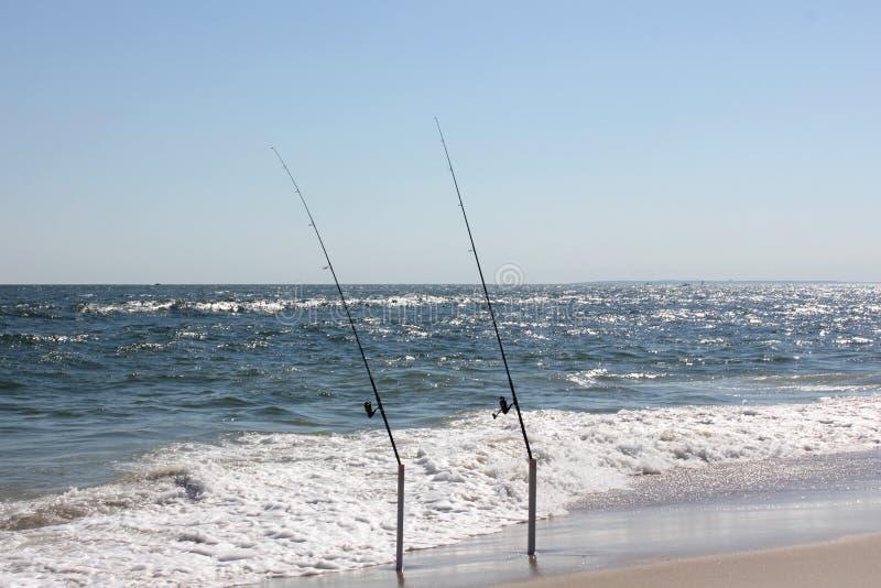 Due canne da pesca sulla spiaggia immagine stock