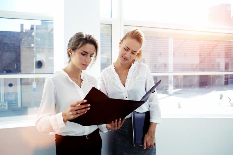 Due capi femminili che analizzano i documenti dopo avere lavorato al cuscinetto di tocco mentre che stanno nell'interno moderno d fotografia stock