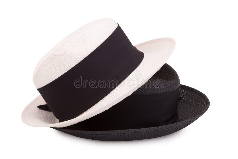 Due cappelli di paglia su una priorità bassa bianca Cappello in bianco e nero immagine stock libera da diritti
