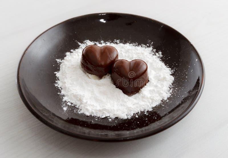 Due caramelle in forma di cuore del cioccolato su un piatto marrone con la polvere dello zucchero contro fondo di legno fotografie stock