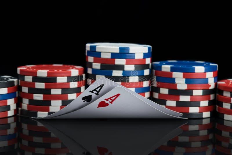 Due carte da gioco e pile ordinate di chip e di loro riflessione in una tavola nera lucida fotografia stock libera da diritti