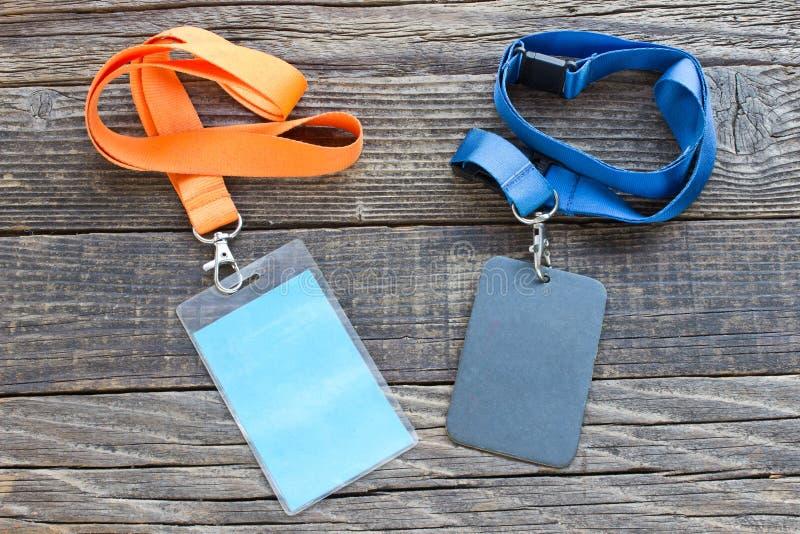 Due carte di identificazione di VIP con le etichette su fondo di legno immagine stock
