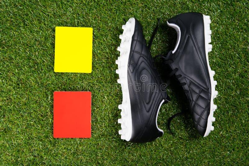 Due carte di pena per l'arbitro e le scarpe di calcio, contro lo sfondo di erba immagine stock libera da diritti
