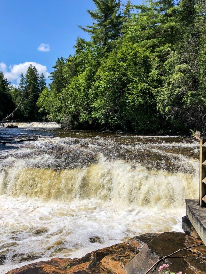 Due cascate che precipitano a cascata giù le rocce nel Michigan superiore fotografia stock libera da diritti