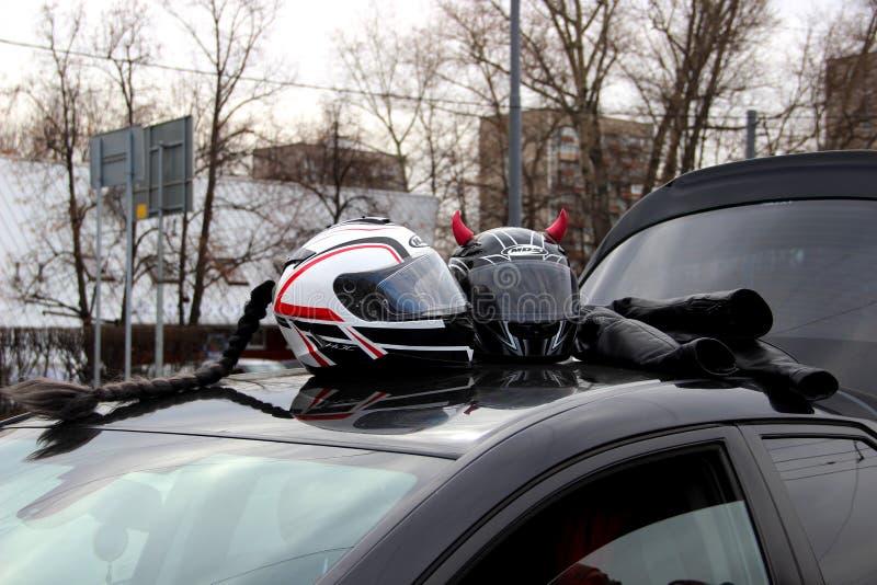 Due caschi del motociclo con i corni rosa ed i capelli intrecciati neri sul tetto di un'automobile Attenzione l'apertura della st fotografie stock