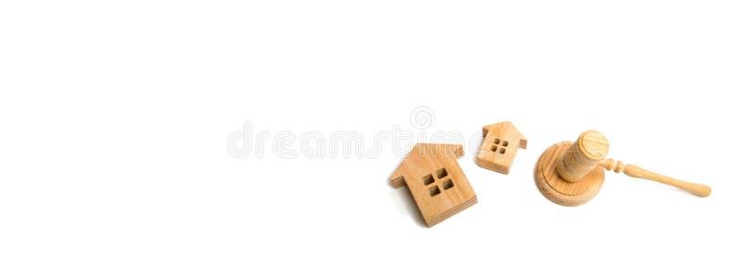 Due case di legno e un martello del giudice su un fondo bianco concetto delle cause in giustizia sulla proprietà e sul bene immob immagini stock